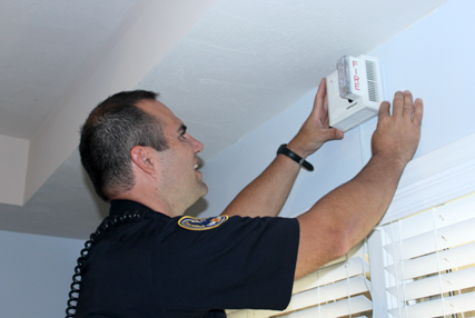 Firefighter installing a smoke alarm.