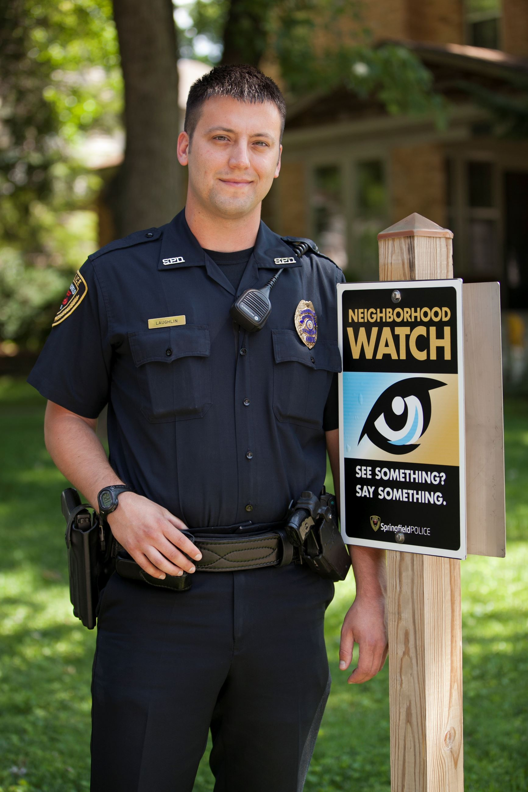 Officer Laughlin with Neighborhood Watch sign