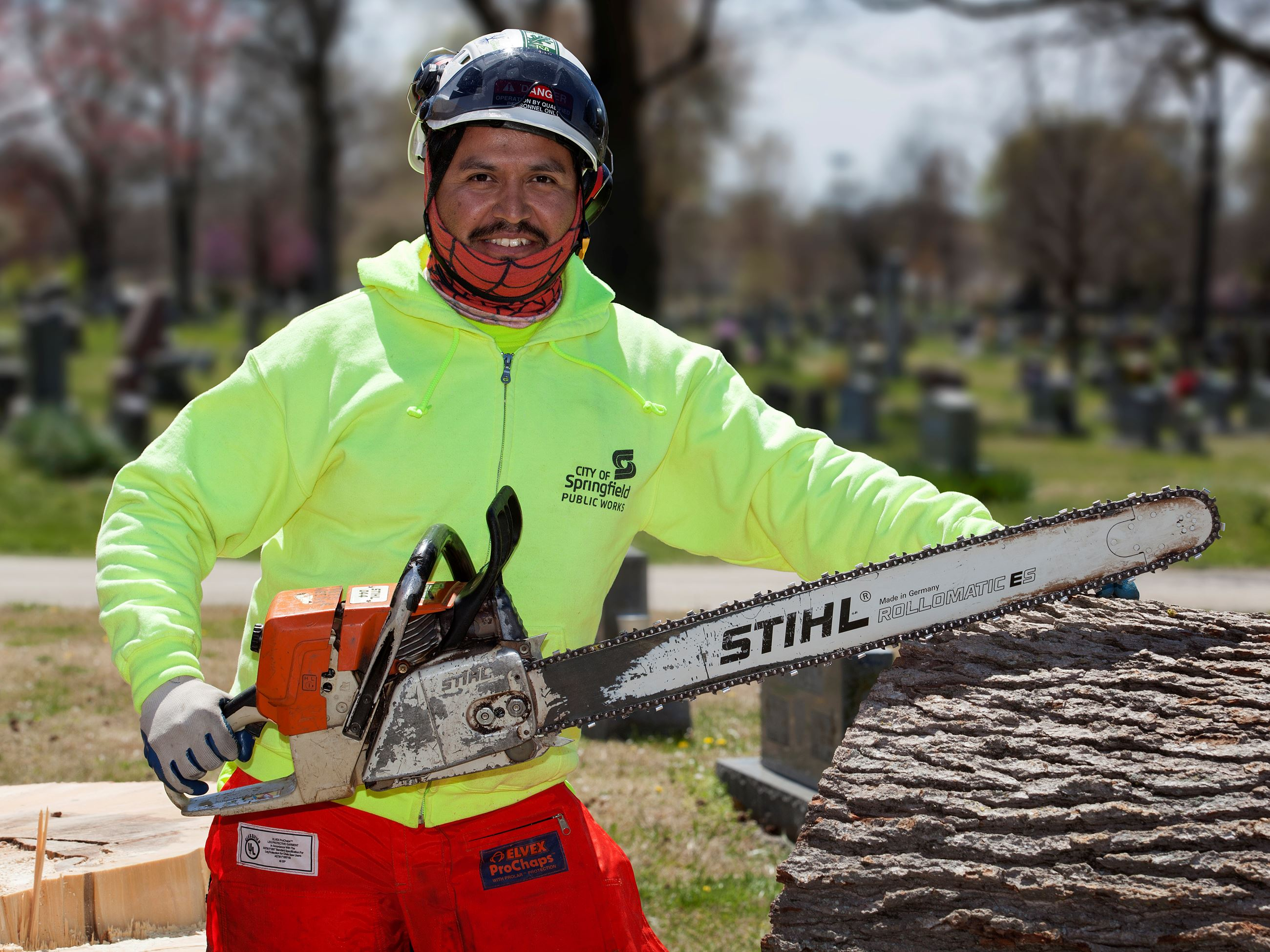outdoor portrait of Edgar Garcia in tree trimming gear, with a large chain saw