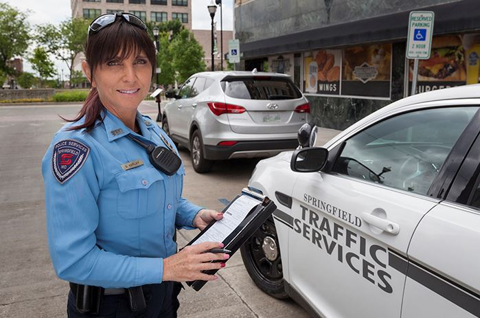 outdoor portrait of traffic services officer, Sheila Kerley, writing a parking ticket