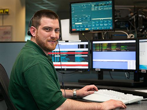 indoor portrait of Andrew Meyer at a 911 emergency desk with multiple monitors behind him