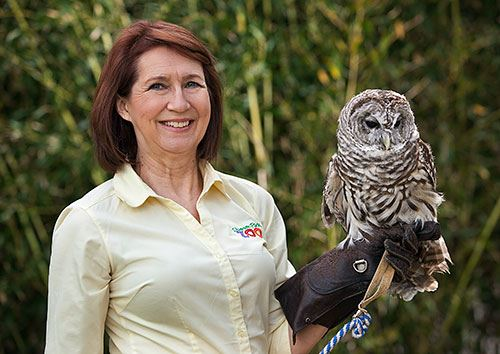 outdoor portrait of Pam Price holding an owl on her glove-protected hand