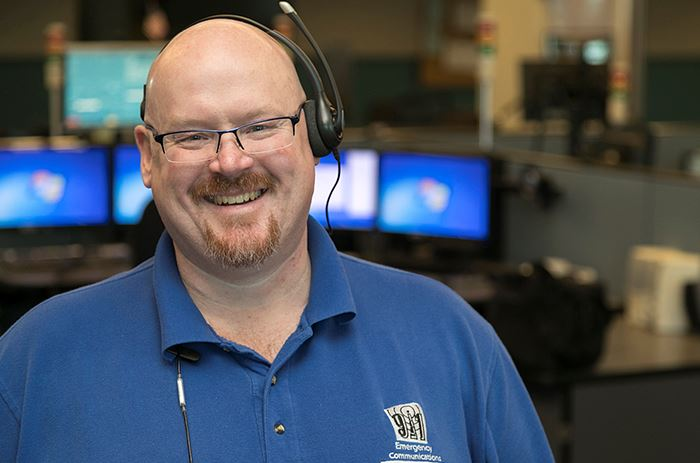environmental portrait of Jim Rayle standing in a 911 dispatch center