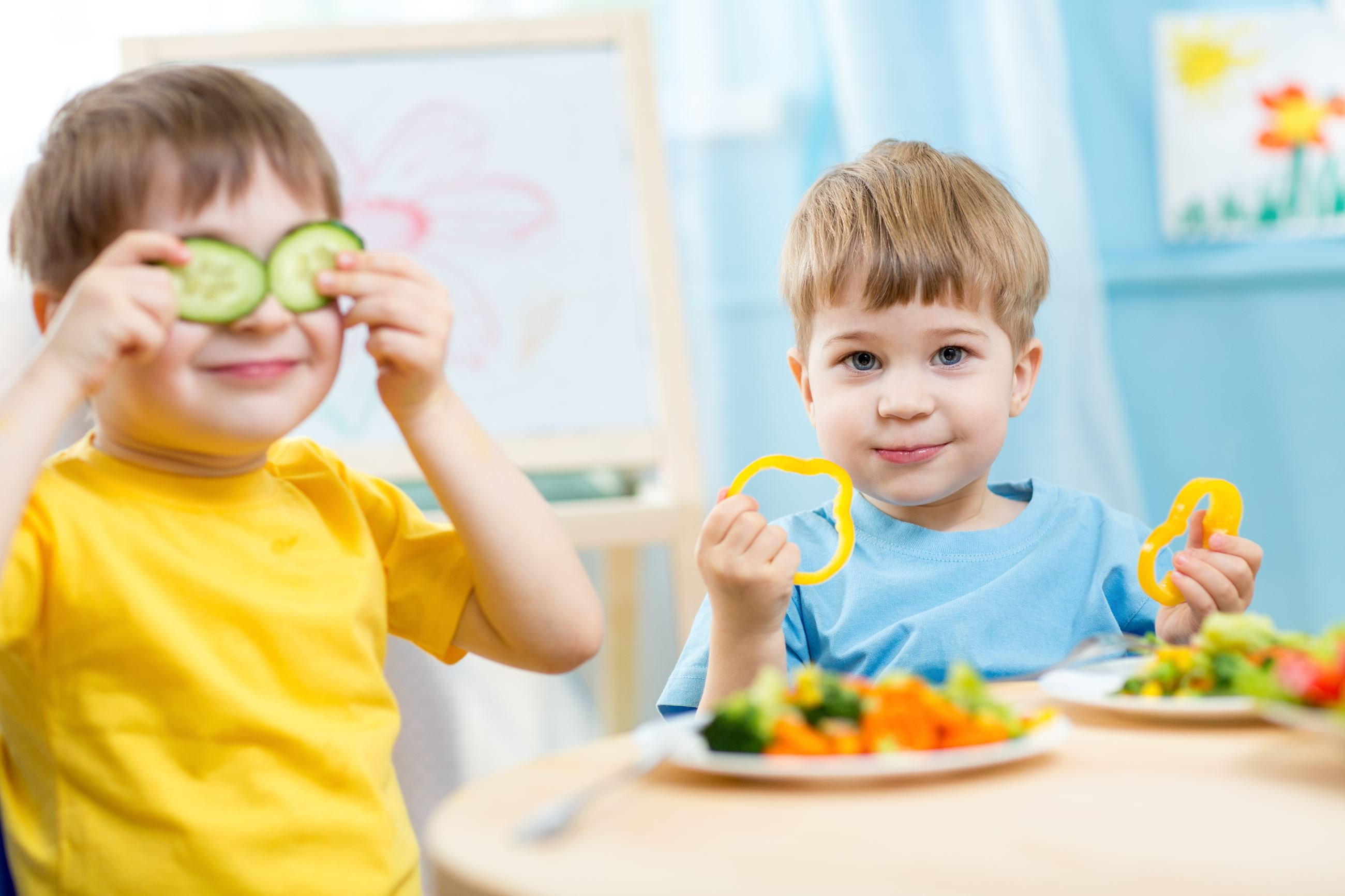 young boy in a yellow shirt plays with his food by putting cucumbers on his eyes; another boy in a b